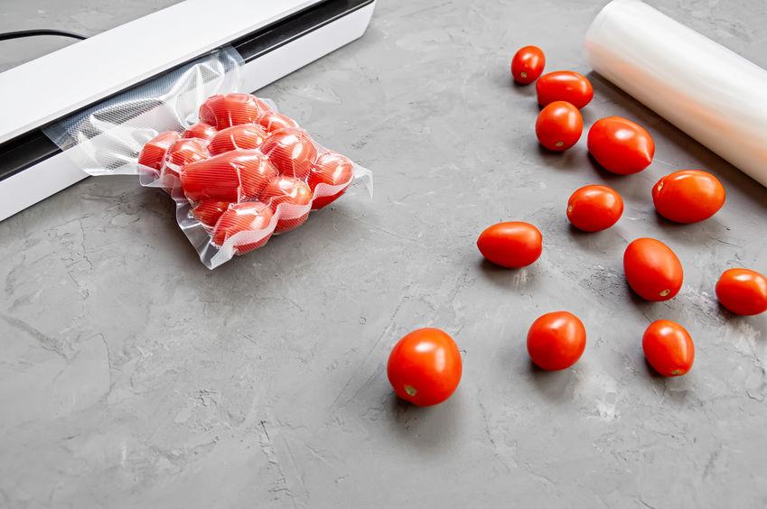 Tomaten werden vorsichtig mit Hilfe eines Vakuumieres vakuumiert